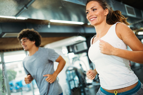 Poster Young attractive woman doing cardio training in gym