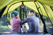 Rear view of asian couple relaxing outside the tent