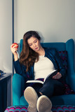 Beautiful woman reading book while relaxing in armchair. - 227908974