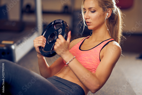 Sticker Sporty woman doing crunches with weight plate. Gym interior.
