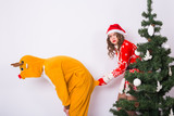 Fun, christmas and holidays concept - funny woman in santa suit holding the tail of man in costume of deer on white background - 227913325