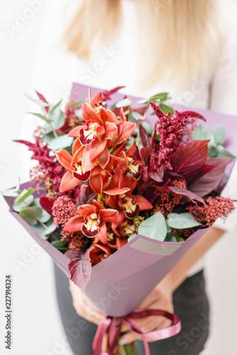 bukiet pomarańczowa orchidea i różni kwiaty. Młoda dziewczyna trzyma kwiaty uzgodnień z różnych kolorów. Biała ściana.