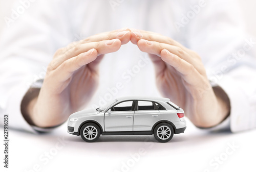 Car insurance. Small silver car covered by hands. - 227916353