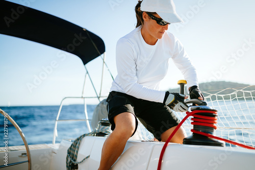 Leinwanddruck Bild Attractive strong woman sailing with her boat