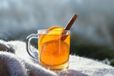 hot tea with orange slices and cinnamon on a wool blanket against a blurred gray blue background with copy space - 227919942