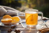 hot ginger tea with orange slices and spices on a wooden table in the sun, healthy drink against cold, copy space - 227920158