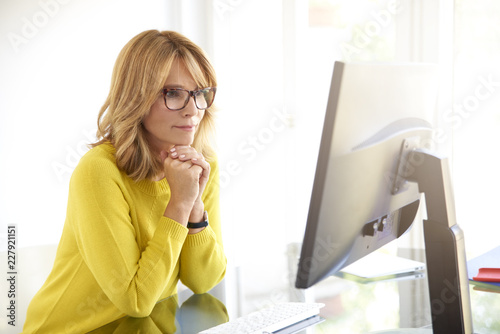 Poster Portrait of serious businesswoman using computer in the office
