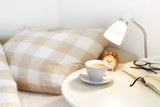 morning coffee on the bedside table, plus an alarm clock, lamp and book with glasses, lazy day concept - 227921988