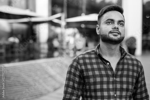 Młody brodaty Indiański biznesmen relaksuje przy centrum handlowym w Bangkok