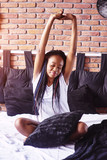 Beautiful black woman waking up in her bed, she is smiling and stretching - 227931399