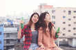 Two asian women drinking at rooftop party, outdoors celebration, friendship, LGBT couple