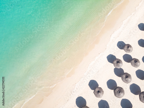 Aerial view of amazing tropical white sandy beach with palm leaves umbrellas and turquoise sea, Mauritius. - 227945111
