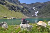 chaussures de randonnée devant un lac Hautes-Alpes, lac de Faravel avec névée, Dormillouse, Alpes, France - 227947529