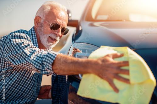 Foto Murales Senior man cleaning his car outdoors