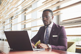 A beautiful stylish African American businesswoman wearing a suit uses his laptop while working - 227952721