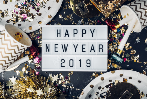 Leinwandbild Motiv Happy new year 2019 on light box with party cup,party blower,tinsel,confetti.Fun Celebrate holiday party time table top view.