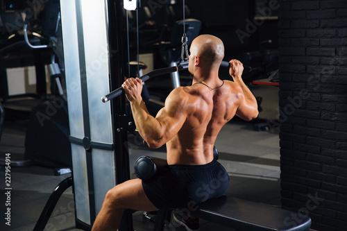 Widok z tyłu, mężczyzna trenuje na siłowni, trenuje na plecach. Mięśniowe plecy sportowca