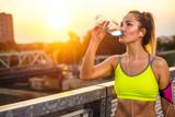 Female runner resting after running on bridge, drinking water