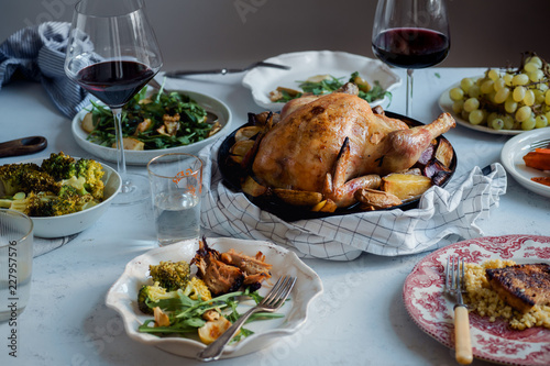 Big festive dinner with roasted chicken, wine and various garnishing. Celebration concept - 227957576