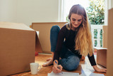 Woman making a list of articles for packing - 227958510