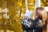 happy young mom with her little newborn daughter in cute pajamas. Walking in autumn Park - 227968533