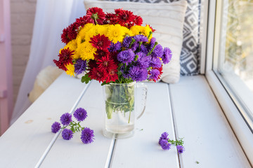Beautiful bright colorful bouquet of multi-colored flowers in a glass vase on a wooden table about a window