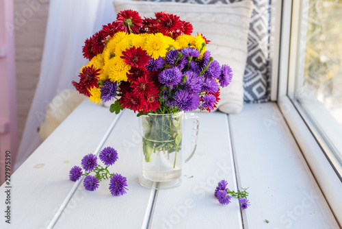 Foto Murales Beautiful bright colorful bouquet of multi-colored flowers in a glass vase on a wooden table about a window