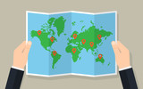 Hands hold folded paper map of world with markers