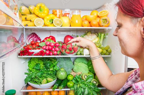 Foto Murales woman picking some fruit on full fridge