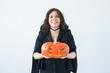 Excited happy young woman in halloween costume posing with carved pumpkin in lightroom