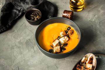 Zupa krem z dyni. Podana z grzankami, pestkami dyni i oliwą.