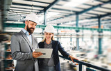 A portrait of an industrial man and woman engineer with tablet in a factory, working. - 227987746