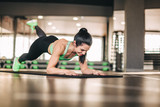 Athletic woman doing exercise on mat - 227991308