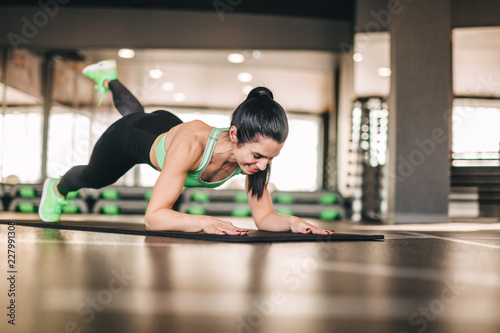 Foto Murales Athletic woman doing exercise on mat