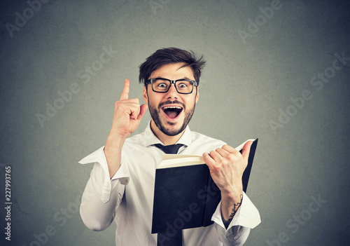 Excited man having idea while reading a book