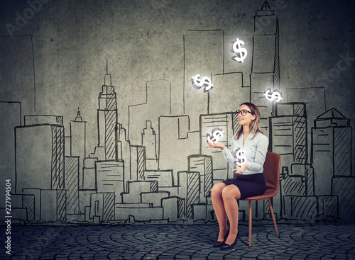 Businesswoman juggling with dollar symbols on a cityscape background