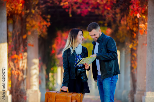 Young man and girl help with navigation in the city for a tourist. Autumn season time
