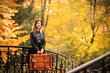 Young white girl with suitcase in a park with yellow trees on background. Autumn season time