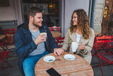 couple holding hands while drinking latte in outdoors cafe - 228055155