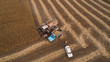 Harvester machine working in field . Old retro harvester unloads soybeans seeds in the truck for transport to a granary. Agriculture. Aerial view. From above.