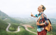 Smiling woman traveler enjoying freedom with up hand on road.
