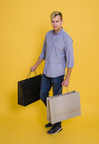 Portrait handsome man holding shopping paper bag over yellow background.