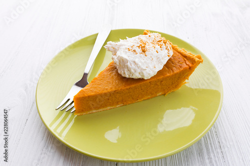 Sticker Slice of pumpkin pie with whipped cream over white wooden background