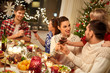 holidays and celebration concept - happy friends having christmas dinner at home, drinking red wine and clinking glasses