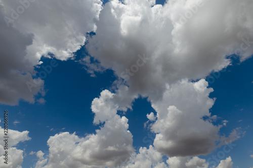 Blue sky, cumulus clouds, sunlight. - 228066926
