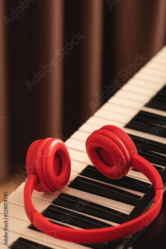 Red headphones over synthesizer keyboard - 228074340