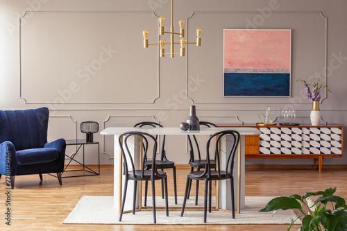 Różowe i granatowe abstrakcyjne malowanie na szarej ścianie z formowaniem w eleganckim wnętrzu jadalni i salonu