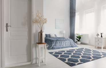 Flower in silver vase on the wooden table next to closed door to elegant new york style bedroom with patterned carpet and white furniture, real photo