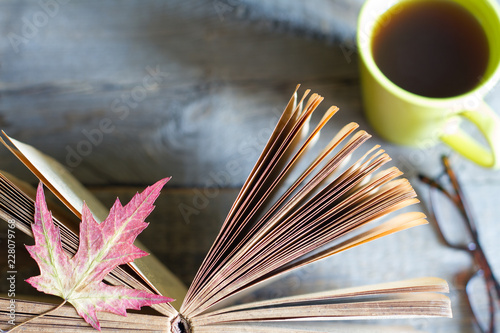 Leinwanddruck Bild Open book autumn leaves tea and glasses abstract background on wooden boards