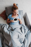 Woman drinking coffee in bed - 228086796